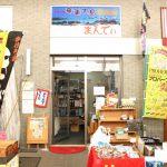 唐人町商店街にある奄美大島物産館まんでぃの外観です。店頭には棚、ワゴンに商品が置かれ、両脇には何本がのぼりがあります。入り口の上部には「奄美大島物産館まんでぃ」と書かれ南国の海が映った看板が掲げられています。