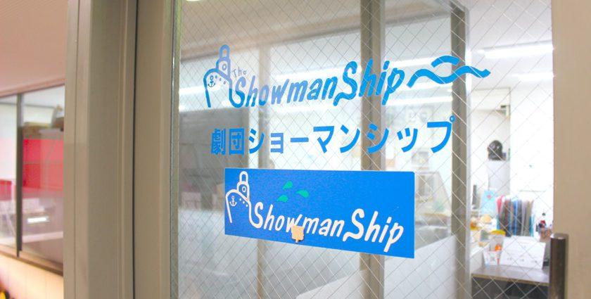 唐人町商店街にある劇団ショーマンシップです。ガラスドアに青字で「Showman Ship 劇団ショーマンシップ」と書かれています。