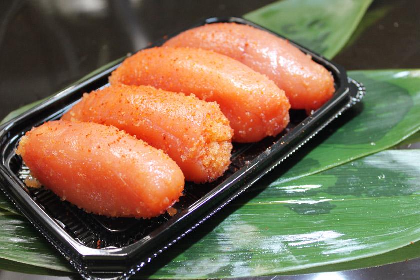 唐人町商店街にある食品店あき乃家唐人町店の人気商品、ご家庭用上切子です。笹の葉の上に、赤味がかった明太子が4切れ、黒い皿の上に盛られています。