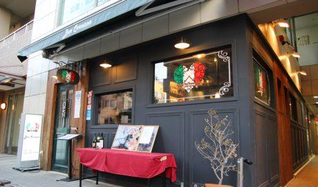 唐人町商店街にあるイタリア&ラテン料理レストラン、バル・コラソンの外観です。店舗の壁は黒色で入り口のドア枠は木製です。窓ガラスにイタリア国旗の配色のハートマークの絵が描かれています。入り口付近には赤いテーブルクロスがかけられた長机があり、ワインボトル、メニュー板が置かれています。