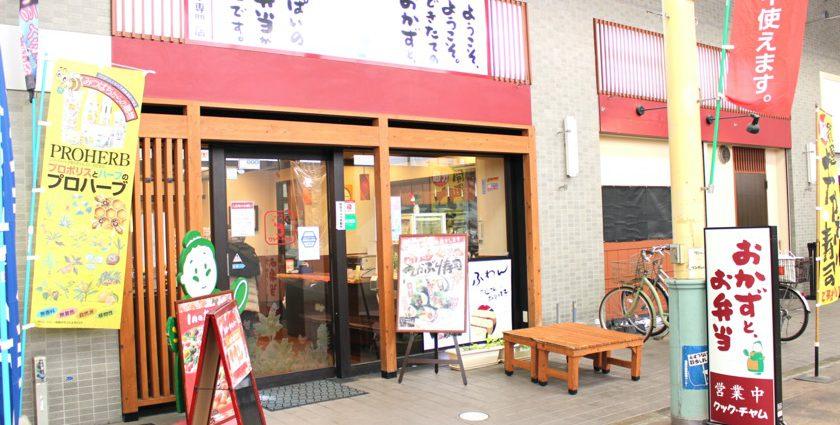 唐人町商店街にあるお惣菜、お弁当のお店クックチャムです。「おかずとお弁当」と書かれたサインが立っています。入り口はガラスのドアで木目調の枠があります。