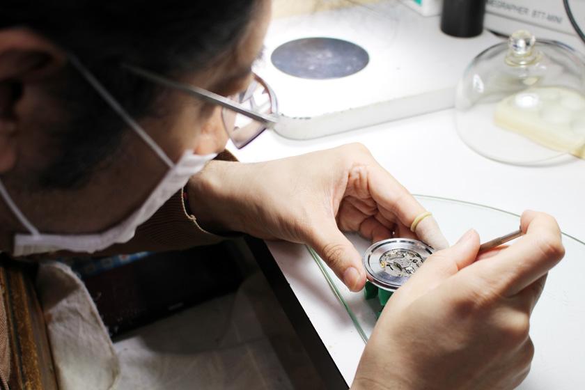 唐人町商店街の時計、メガネ、貴金属の専門店ダイシンで、店主が時計の修理をしています。