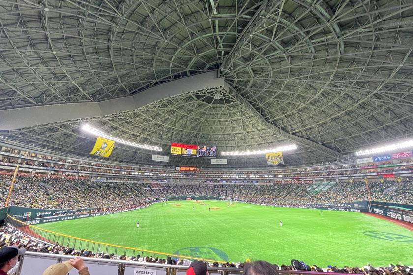 福岡ソフトバンクホークスの本拠地、福岡PayPayドームです。外野席からの眺めで、鮮やかな緑色のグラウンドの回りを観客席が囲んでいます。上部は閉会式の大きな屋根に覆われています。