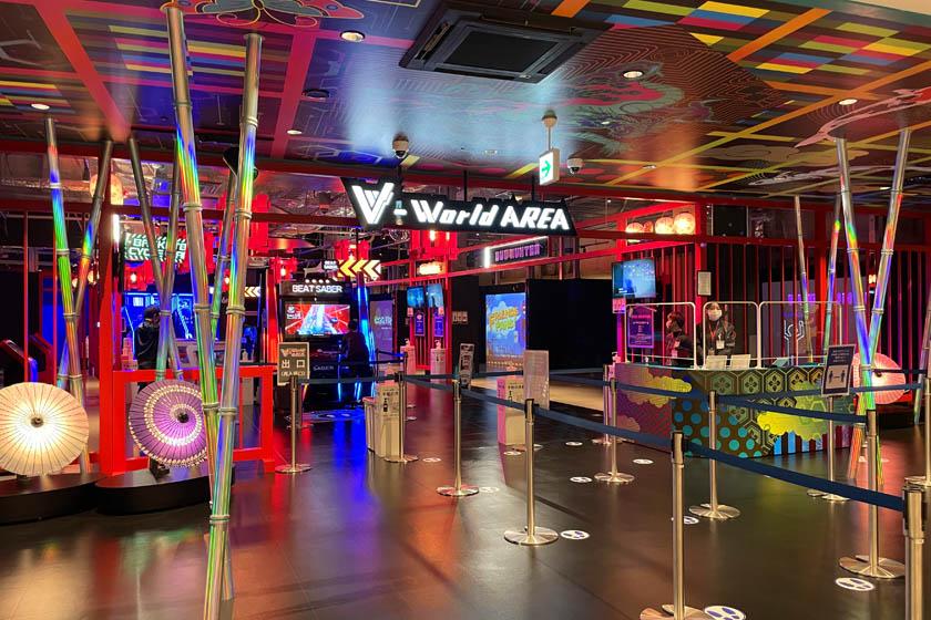 BOSS E・ZO FUKUOKA内にあるアトラクションV-World AREAの入り口です。奥にはテレビゲーム画面があり、赤、青、緑などカラフルな光の装飾がなされています。