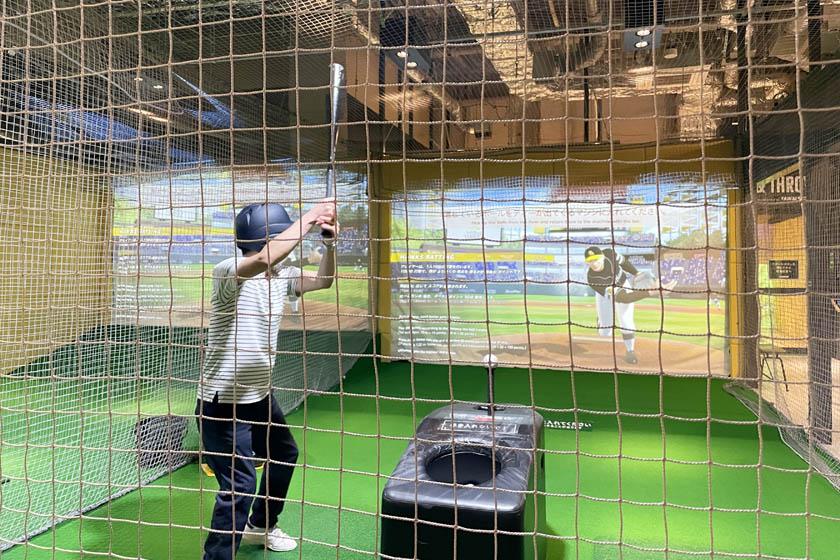 BOSS E・ZO FUKUOKA内にあるアトラクション「王貞治ベースボールミュージアム」にある89パークのホークスティーバッティングです。男性の大人が映像の投手の動きに合わせてバッティングをしようと構えています。
