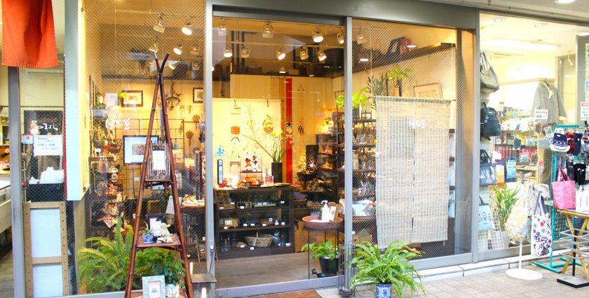 唐人町商店街にあるギャラリー風知草の外観です。ガラス張りで店内には棚に飾られたたくさんの商品があります。