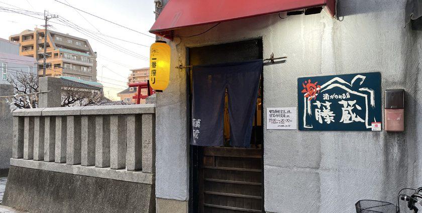 唐人町商店街にある酒が飲める店 藤蔵の外観です。赤い庇に紺色の暖簾がかかっています。左側に提灯、右側に「酒が飲める店 藤蔵」と書かれた看板が設置されています。