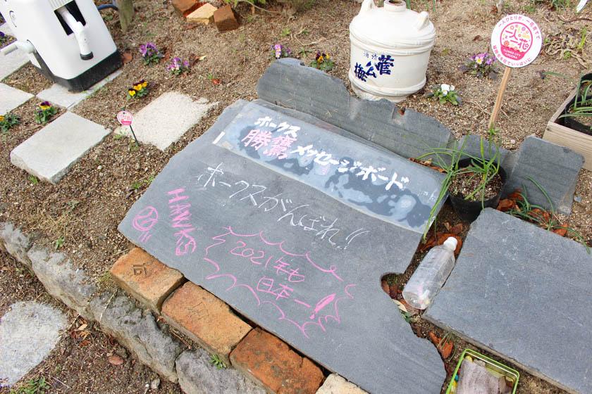 ホークスとうじん通りガーデンの花壇の中に設置されているホークス勝鷹メッセージボードです。「ホークスがんばれ」、「HAWKS」、「2021年も日本一!」と書かれています。
