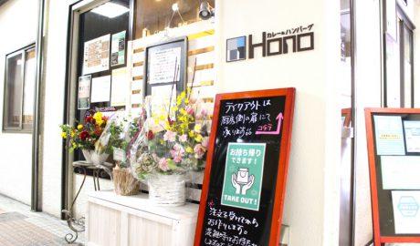 唐人町商店街にあるカレー&フレンチトースト Honoの外観です。白色の壁に「カレー&ハンバーグ HONO」と書いてあります。いくつかの花束が棚の上に置かれています。「テイクアウトは厨房側の扉にて承ります」と書かれた看板が立てかけられています。