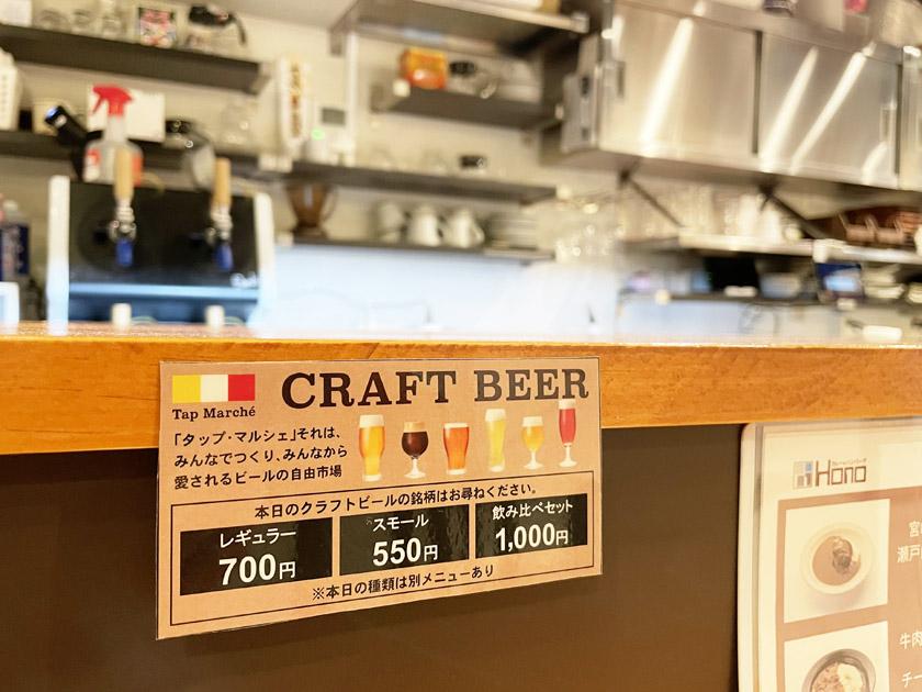 唐人町商店街にあるカレー&フレンチトースト Honoの店内です。木目調のカウンターに飲料のメニューが貼ってあり、「CRAFT BEER レギュラー700円 スモール550円 飲み比べセット1,000円」などが書かれています。