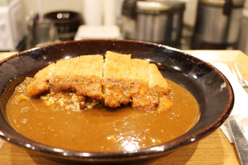 唐人町商店街にあるカレー&フレンチトースト Honoの料理、宮崎きなこ豚カツカレーです。茶色の皿にカレー盛られ、カツが乗っています。