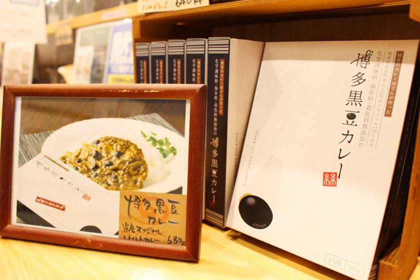 唐人町商店街にあるカレー&フレンチトースト Honoの店内で売られている博多黒豆カレーのパッケージです。左側には博多黒豆カレーの写真が飾られています。