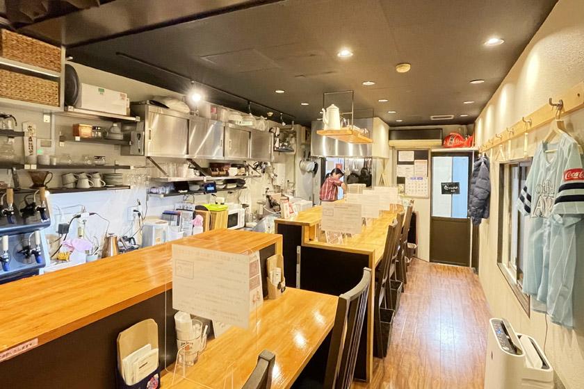 唐人町商店街にあるカレー&フレンチトースト Honoの店内です。木目調のカウンターが店内にのびています。カウンターの左側はキッチンで、奥に店主が調理をしています。右側に福岡ソフトバンクホークスの青いユニフォームがハンガーにかけられています。