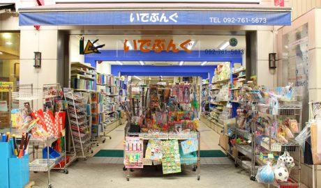 唐人町商店街にある文房具店 井手文具の外観です。ひさしには「いでぶんぐ TEL 092-761-5673」と書かれています。店頭には子供用のプラスチック製のバットやボール、おもちゃなどが展示されています。