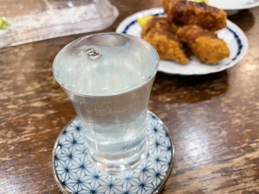 西公園商工連盟の酒場まぐろやジョーの店内です。日本酒 田中六五がグラスいっぱいに注がれています。奥にはまぐろカツがあります。