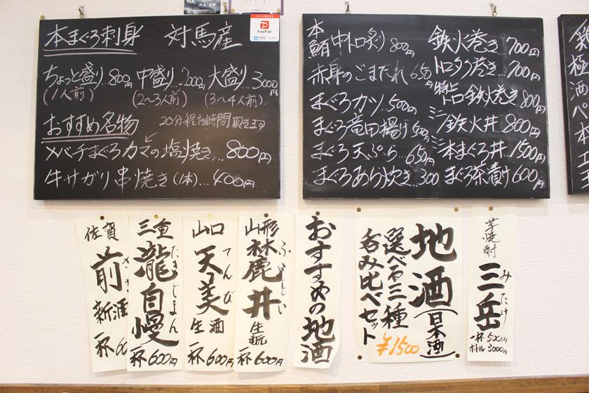西公園商工連盟の酒場まぐろやジョーの店内です。壁にメニューが書かれています。本まぐろ刺身 対馬産、まぐろカツ500円、まぐろ天ぷら650円、地酒(日本酒)などと書かれています。