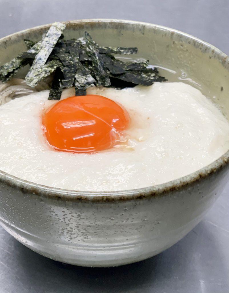 西公園商工連盟の加辺屋西公園店のメニュー、宇賀の月です。蕎麦に海苔と、生卵が乗ったとろろ芋がかかっています。
