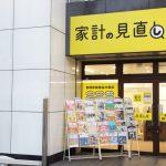 唐人町商店街にある家計の見直し堂 福岡唐人町駅前店の外観です。壁に黄色い看板に家計の見直し堂と書かれています。入り口にはパンフレットラックがあり、たくさんのチラシが配置されています。
