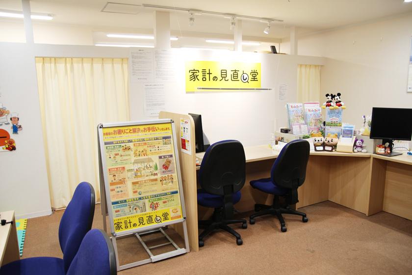 唐人町商店街にある家計の見直し堂 福岡唐人町駅前店の店内です。壁に黄色い看板に家計の見直し堂と書かれています。木目調の机に青色の椅子が並んでいます。中央には案内板が置かれています。