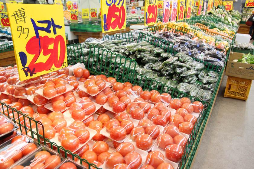 唐人町商店街にある青果店ママキッチンの店内です。袋詰めされたトマト、きゅうり、なすなどが並んでいます。博多トマト1PK250円、きゅうり1袋150円と書かれています。