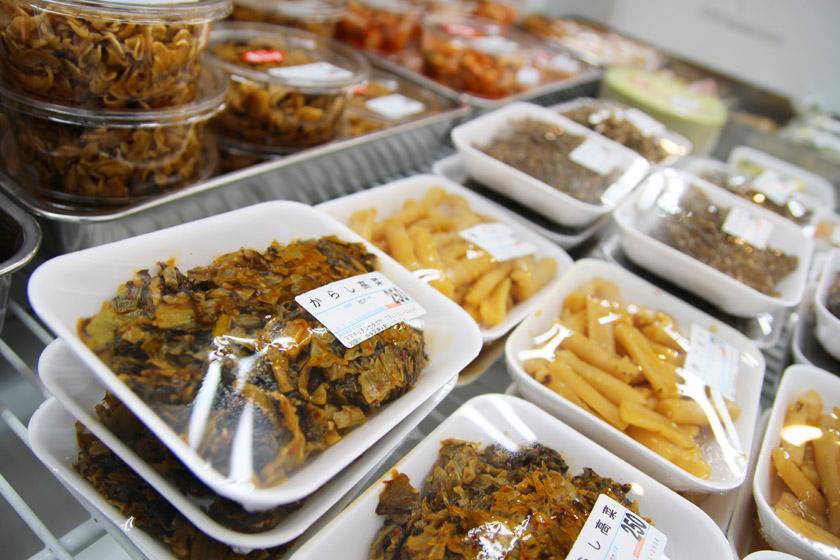 唐人町商店街にある青果店ママキッチンの店内です。白いパックにからし高菜と書かれた惣菜などが並んでいます。