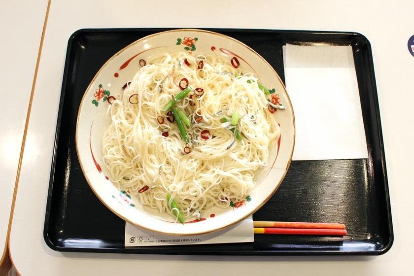 唐人町商店街にある奄美大島物産館/喫茶・居酒屋 まんでぃの人気メニュー、油ソーメンです。薄い皿の盛られた素麺に煮干し、唐辛子、ニラがからんでいます。