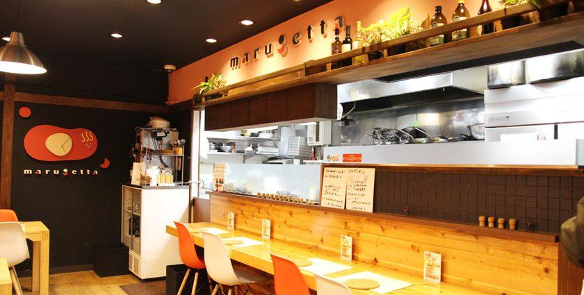 唐人町商店街にあるパスタ店マルゲッタの店内です。木目調のテーブルに白、オレンジ色の椅子が並んでいます。壁にはmarugettaと書かれています。