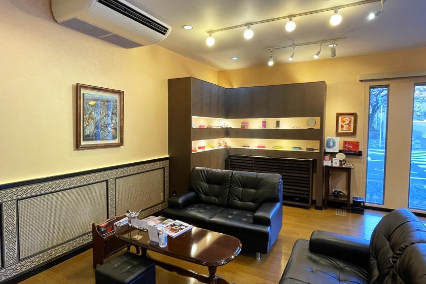 西公園商工連盟のメガネショップ松葉屋の店内です。中央に黒いソファーと茶色の机、奥には眼鏡が展示されている茶色の棚があります。壁には絵が飾られています。