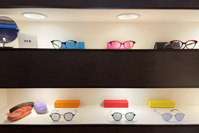 西公園商工連盟のメガネショップ松葉屋の店内です。棚にはメガネが6つ並んでいます。オレンジ、赤、黄などカラフルなメガネケースも置かれています。