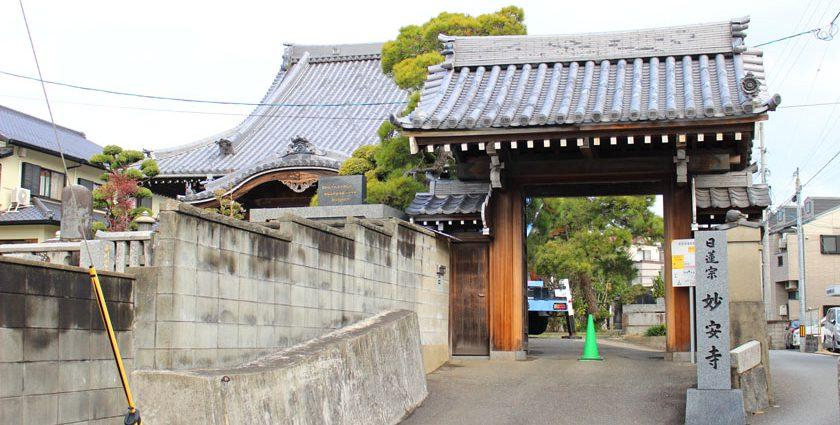 唐人町にある妙案寺です。中央に山門があり、山門の手前に日蓮宗妙案寺と書かれた石柱が立っています。奥に本殿があります。