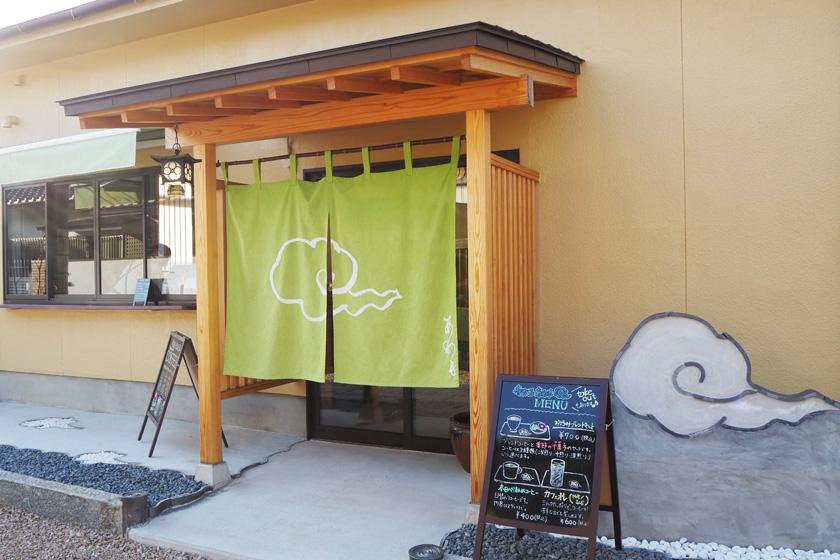 唐人町にある妙法寺の「寺カフェ あわも」の外観です。入り口には、緑色の暖簾があり、右側にメニューが書かれた看板があります。