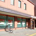 唐人町商店街にある西日本シティ銀行唐人町支店の外観です。右側に西日本シティ銀行と書かれたがあります。店舗の壁は薄いオレンジ色で、1階の窓には緑色のブラインドがしてあります。店頭に自転車が2台とまっています。
