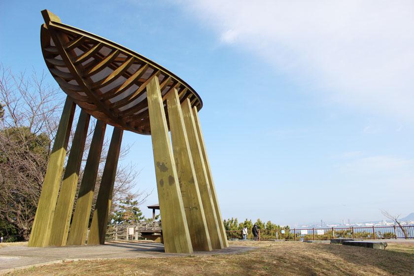 福岡市西公園の中央展望台にある木製の大きなオブジェです。青空とともに博多湾の対岸が見えます。