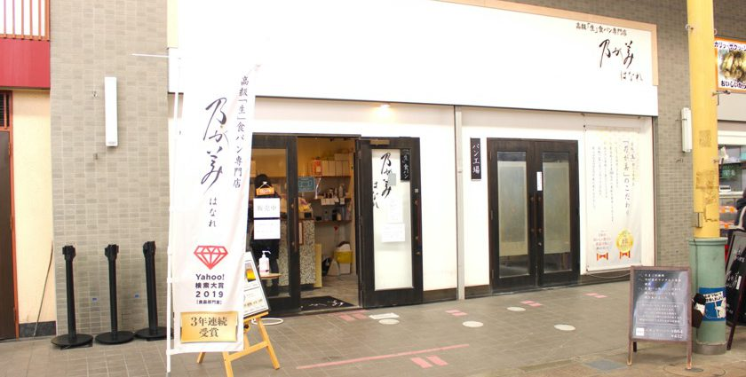 唐人町商店街にある乃が美 はなれ 福岡店の外観です。白地の壁に「高級生食パン専門店乃が美はなれ」と書かれています。