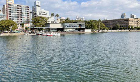 福岡市にある大濠公園で、大きな池の周囲はジョギング、ウオーキングができる歩道があります。中央にはレストランがあり、その左側には貸しボートが何艘か湖面に浮かんでいます。