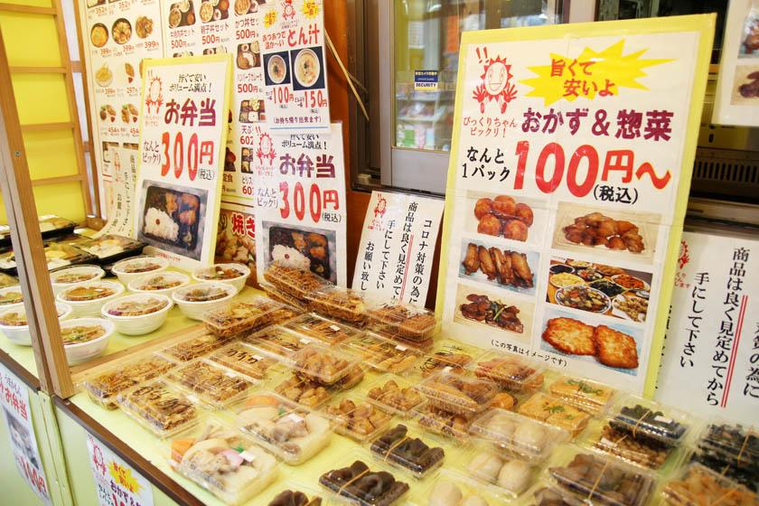 唐人町商店街にあるお食事ランドの店頭です。パック詰めされたお惣菜、弁当が並んでいます。看板がいくつかあり、「旨くて安いよ おかず&惣菜 なんと1パック100円(税込)〜」などと書かれています。