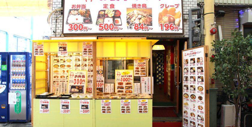 唐人町商店街にあるお食事ランドの外観です。店頭にはパック詰めされたお惣菜、弁当が並んでいます。店舗の上部には「お食事ランド お弁当300円〜 定食500円〜 焼き鳥1本84円〜 クレープ196円〜」と書かれた看板があります。