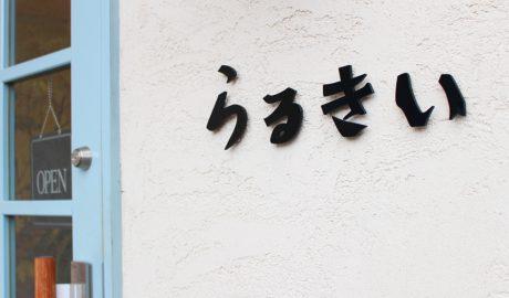 西公園商工連盟のパスタとピザの専門店らるきいの入り口です。白い壁に「らるきい」と黒字で書かれています。