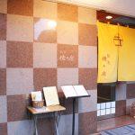 西公園商工連盟の鮨処佐々庄のお店です。市松模様の外観に、鮮やかな黄色の暖簾がかけられています。