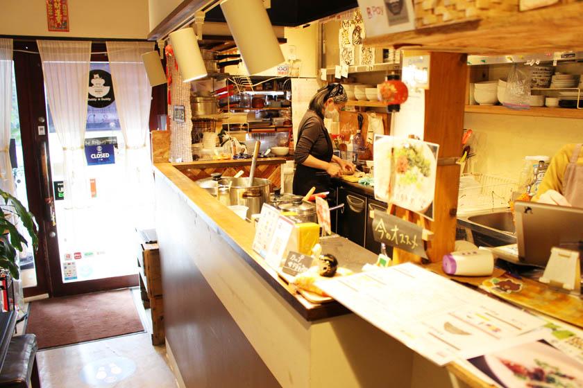 西公園商工連盟の「福岡のお粥カフェTeddy & Daddyテディ&ダディ」の店内です。カウンターの奥がキッチンとなっていて、店長さんが調理をしています。