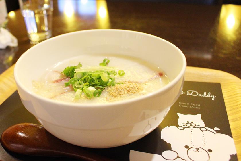 西公園商工連盟の「福岡のお粥カフェTeddy & Daddyテディ&ダディ」の料理、中華風鯛粥です。白い器に入ったお粥には、ネギ、ごまがかけられています。