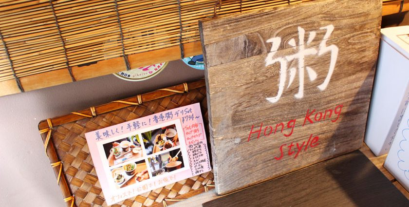 西公園商工連盟の「福岡のお粥カフェ Teddy & Daddy テディ&ダディ」の店内に飾られている看板です。木板に「粥 Hong Kong Style」と書かれています。隣に「美味しく!手軽に!香港粥デリSet 734円」と書かれた写真が掲示されています。