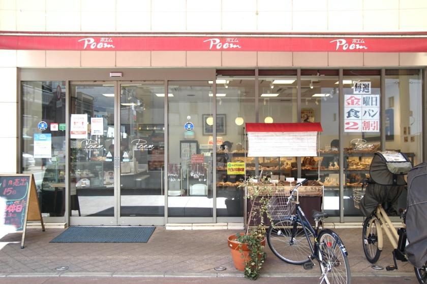 唐人町商店街にある唐人ベーカリー ポエム本店の外観です。赤いひさしにはPoemポエムと書かれています。ガラス張りで店頭には自転車がとめられています。