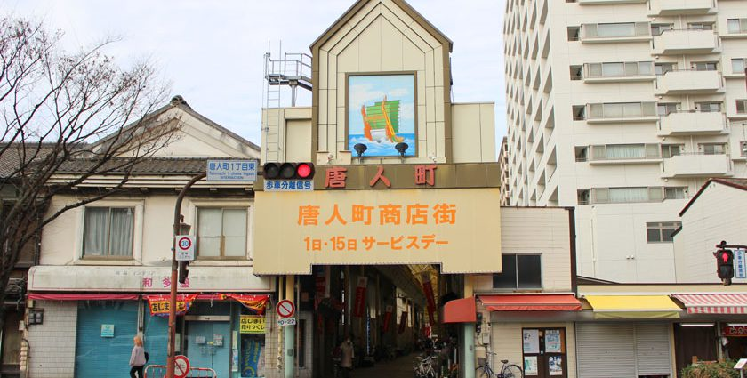 唐人町商店街にあるアーケードの東側入り口です。唐人町商店街 1日・15日サービスデー、唐人町と書かれた文字の上部に遣唐使船の絵が描かれています。アーケード内、および入り口の両側に店舗が並んでいます。
