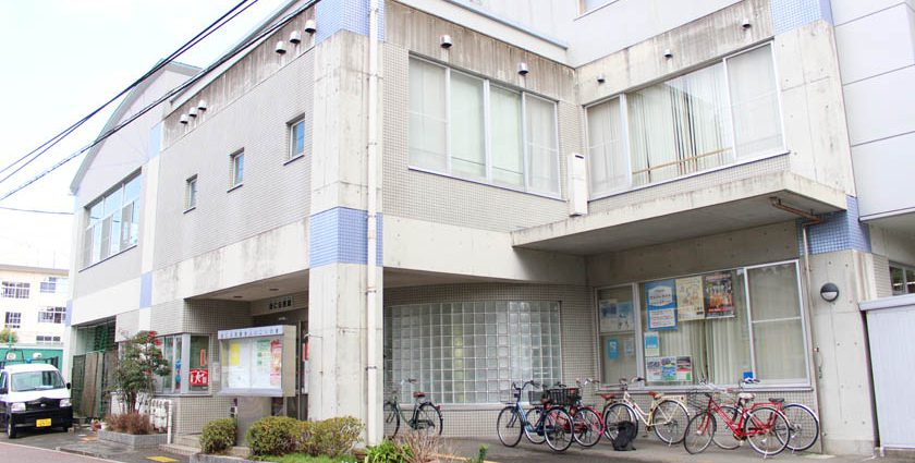 福岡市中央区の当仁公民館の外観です。コンクリート造りの建物です。駐輪スペースに自転車が何台かあります。