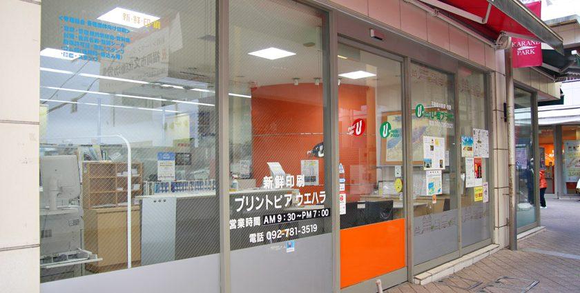唐人町商店街にある印刷会社プリントピア・ウエハラの外観です。ガラス張りの外壁に「新鮮印刷 プリントピア・ウエハラ 営業時間AM9:30-PM7:00 電話092-781-3519」と書かれています。