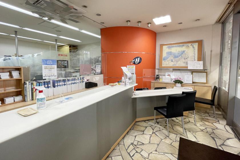 唐人町商店街にある印刷会社プリントピア・ウエハラの店内です。中央にオレンジ色の円形の柱があり、白いカウンターが奥から手前にのびています。