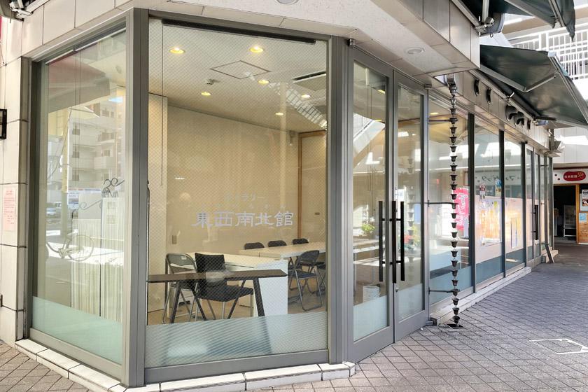 唐人町商店街にある印刷会社プリントピア・ウエハラが運営する貸しスペース東西南北館の外観です。ガラス張りの外壁に、ギャラリー東西南北館と書かれています。