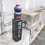 「ヤクルト事業創業の地」の記念碑です。記念碑の上部はヤクルト飲料の容器の形をしています。下部には、「健腸長寿 代田 稔」、「ヤクルト事業創業の地 昭和10年(1935年)」と書かれています。