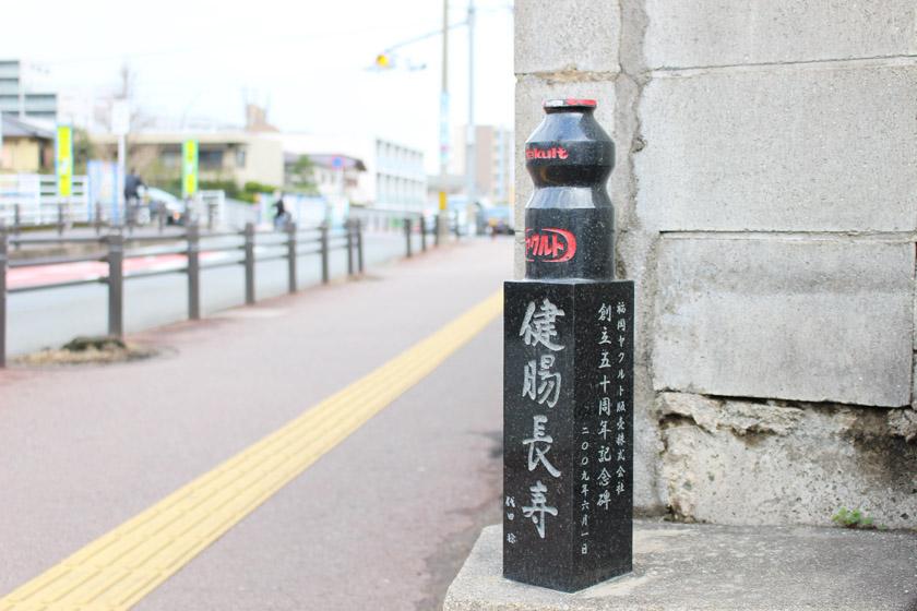 「ヤクルト事業創業の地」の記念碑です。記念碑の上部はヤクルト飲料の容器の形をしています。下部には、「健腸長寿 代田 稔」、「福岡ヤクルト販売株式会社 創立50周年記念碑 2009年6月1日」と書かれています。